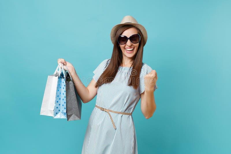Μοντέρνη ελκυστική ευτυχής γυναίκα πορτρέτου στο θερινό φόρεμα, καπέλο αχύρου, γυαλιά ηλίου που κρατά τις τσάντες συσκευασιών με  στοκ φωτογραφία