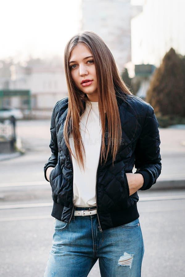 Μοντέρνη νέα γυναίκα που θέτει το εξωτερικό στην οδό πόλεων στοκ εικόνες