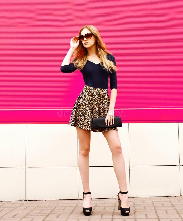 Μοντέρνη ξανθή πρότυπη τοποθέτηση γυναικών στη φούστα λεοπαρδάλεων, γυαλιά ηλίου με το συμπλέκτη τσαντών στην οδό πόλεων στοκ εικόνες με δικαίωμα ελεύθερης χρήσης