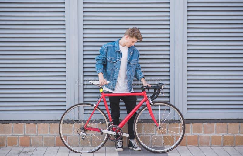Μοντέρνος νεαρός άνδρας με ένα ποδήλατο στο οποίο η διαπερασμένη ρόδα στέκεται στα πλαίσια του τοίχου στοκ φωτογραφία με δικαίωμα ελεύθερης χρήσης