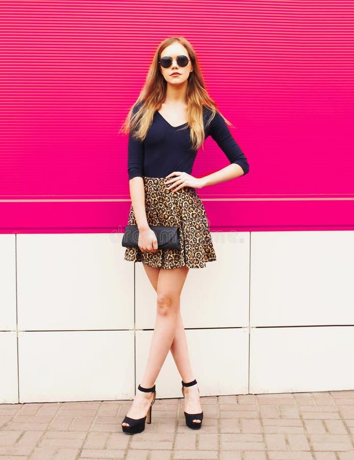 Μοντέρνο νέο ξανθό πρότυπο γυναικών στη φούστα λεοπαρδάλεων, γυαλιά ηλίου με την τοποθέτηση συμπλεκτών τσαντών στην οδό πόλεων στοκ φωτογραφία