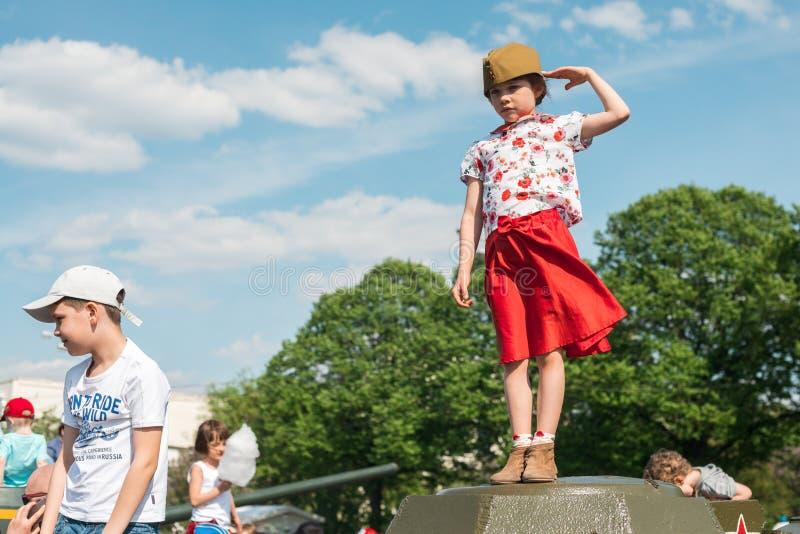 ΜΟΣΧΑ, ΡΩΣΙΑ - 9 ΜΑΐΟΥ 2016 Το μικρό κορίτσι σε μια κόκκινες φούστα και μια χορτονομή-ΚΑΠ στέκεται σε μια δεξαμενή του δεύτερου π στοκ εικόνες