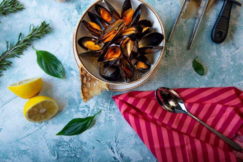 Μύδια στο πιάτο που εξυπηρετείται με τις ντομάτες, τη φρυγανιά και το λεμόνι στοκ εικόνες