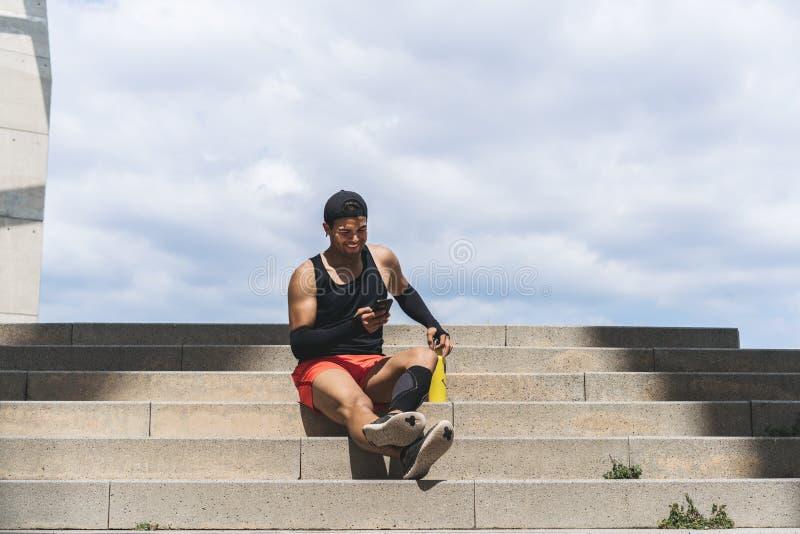 Μυϊκό κατάλληλο αθλητικό πρότυπο χαμόγελου sprinter που στηρίζεται μετά από το workout του και χρησιμοποίηση του κινητού τηλεφώνο στοκ εικόνες