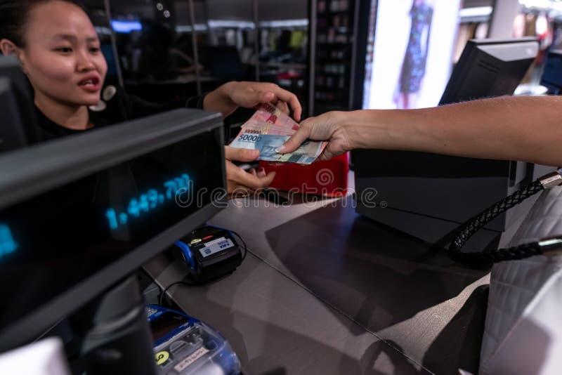 ΜΠΑΛΙ, ΙΝΔΟΝΗΣΙΑ - FEBRAURY 19, 2019: Νέα γυναίκα που δίνει τα χρήματα στον ταμία στο κατάστημα μόδας στοκ φωτογραφία με δικαίωμα ελεύθερης χρήσης