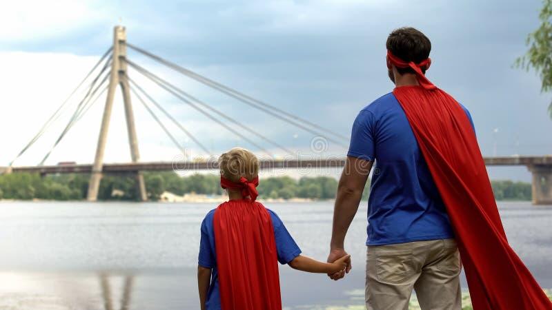 Μπαμπάς και γιος ως ομάδα υπερανθρώπων που εξετάζει την πόλη, που παρακινείται για το επιτυχές μέλλον στοκ φωτογραφίες