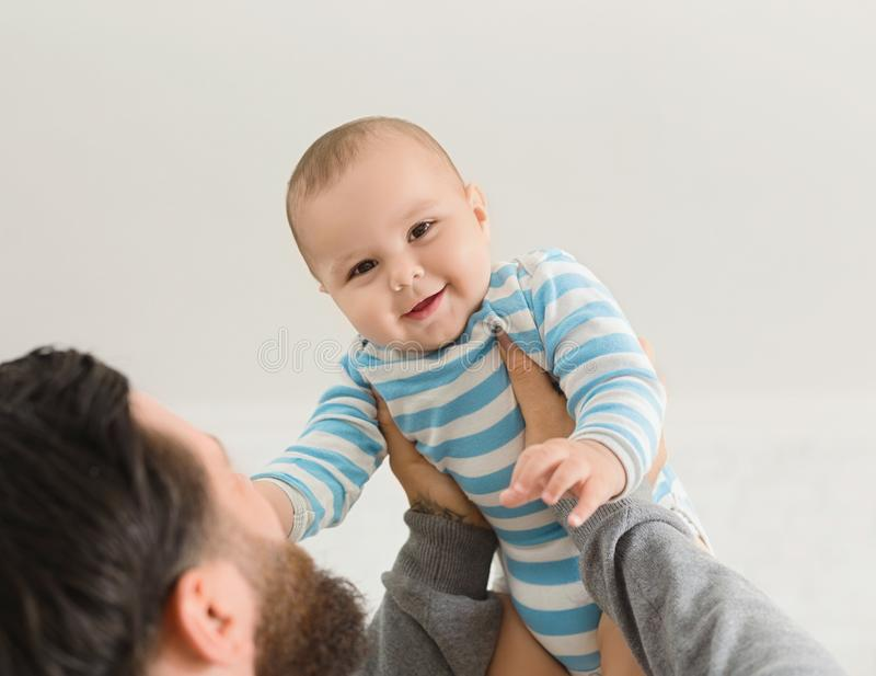 Μπαμπάς που κρατά τον ευτυχή γιο μωρών επάνω στον αέρα στοκ φωτογραφία με δικαίωμα ελεύθερης χρήσης
