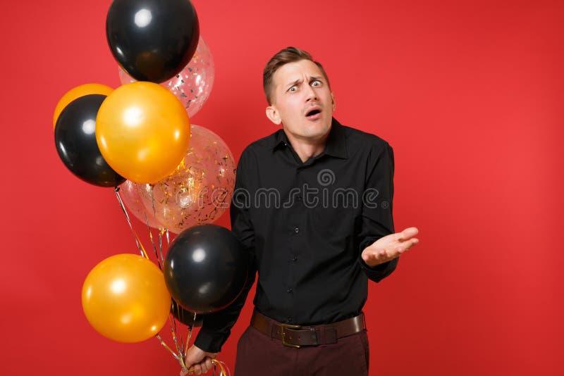 Μπερδεμένος νεαρός άνδρας στα μαύρα κλασικά μπαλόνια αέρα εκμετάλλευσης πουκάμισων, χέρια διάδοσης στο φωτεινό κόκκινο υπόβαθρο S στοκ εικόνα με δικαίωμα ελεύθερης χρήσης