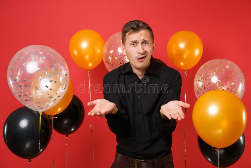 Μπερδεμένος νεαρός άνδρας στα μαύρα κλασικά χέρια διάδοσης πουκάμισων στα φωτεινά κόκκινα μπαλόνια αέρα υποβάθρου Βαλεντίνος ` s  στοκ εικόνα με δικαίωμα ελεύθερης χρήσης