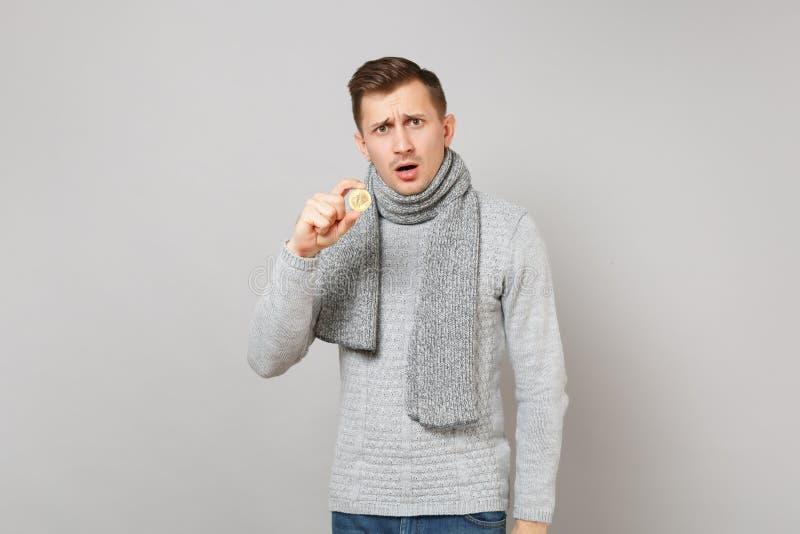 Μπερδεμένος νεαρός άνδρας στο γκρίζο πουλόβερ, εκμετάλλευση μαντίλι bitcoin, μελλοντικό νόμισμα που απομονώνεται στο γκρίζο υπόβα στοκ φωτογραφία με δικαίωμα ελεύθερης χρήσης