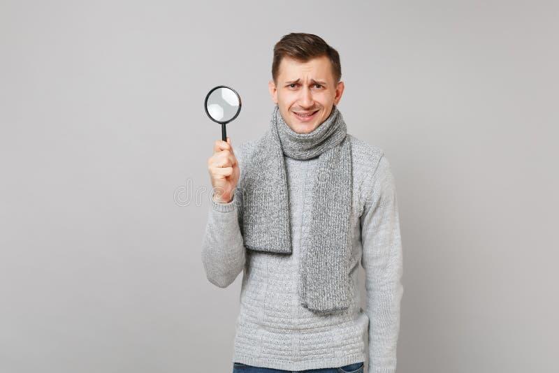 Μπερδεμένος νεαρός άνδρας στο γκρίζο πουλόβερ, ενίσχυση εκμετάλλευσης μαντίλι - γυαλί στο γκρίζο υπόβαθρο τοίχων στο στούντιο Υγι στοκ εικόνες με δικαίωμα ελεύθερης χρήσης