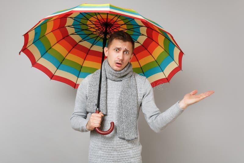 Μπερδεμένος νεαρός άνδρας στο γκρίζο πουλόβερ, ζωηρόχρωμη ομπρέλα λαβής μαντίλι, που δείχνει το χέρι κατά μέρος στο γκρίζο υπόβαθ στοκ εικόνα