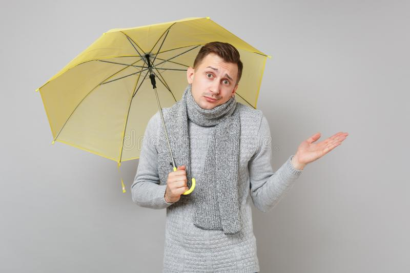 Μπερδεμένος νεαρός άνδρας στο γκρίζο πουλόβερ, κίτρινο χέρι διάδοσης ομπρελών λαβής μαντίλι στο γκρίζο υπόβαθρο Υγιής στοκ φωτογραφία