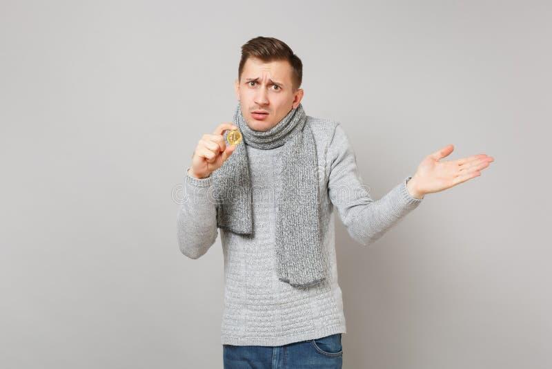 Μπερδεμένος νεαρός άνδρας στο γκρίζο πουλόβερ, λαβή μαντίλι bitcoin, μελλοντικό νόμισμα, χέρια διάδοσης στο γκρίζο υπόβαθρο στοκ φωτογραφία με δικαίωμα ελεύθερης χρήσης