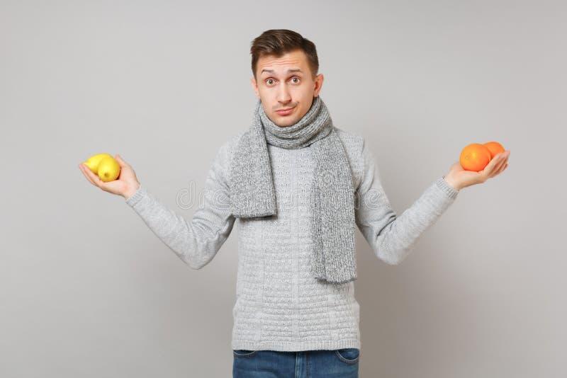 Μπερδεμένος νεαρός άνδρας στο γκρίζο πουλόβερ, λεμόνια πορτοκαλιών εκμετάλλευσης μαντίλι στο γκρίζο υπόβαθρο τοίχων στο στούντιο  στοκ φωτογραφία με δικαίωμα ελεύθερης χρήσης