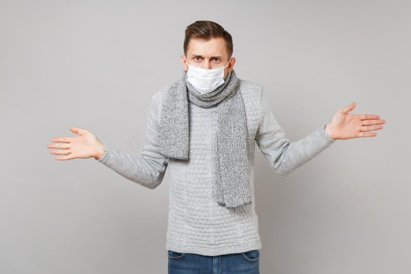 Μπερδεμένος νεαρός άνδρας στο γκρίζο πουλόβερ, μαντίλι με τα αποστειρωμένα χέρια διάδοσης μασκών προσώπου στο γκρίζο υπόβαθρο Υγι στοκ εικόνες με δικαίωμα ελεύθερης χρήσης