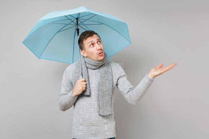Μπερδεμένος νεαρός άνδρας στο γκρίζο πουλόβερ, μαντίλι που δείχνει το χέρι κατά μέρος, που κρατά την μπλε ομπρέλα στο γκρίζο υπόβ στοκ φωτογραφία με δικαίωμα ελεύθερης χρήσης