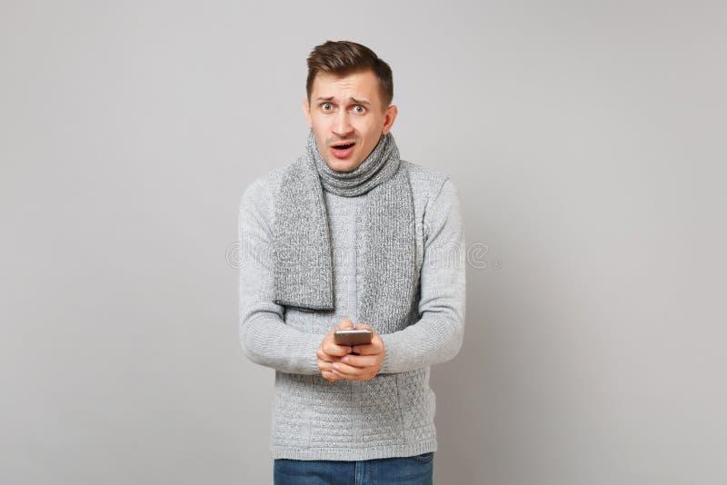 Μπερδεμένος νεαρός άνδρας στο γκρίζο πουλόβερ, μαντίλι που χρησιμοποιεί το κινητό μήνυμα τηλεφωνικής δακτυλογράφησης sms στο γκρί στοκ εικόνα με δικαίωμα ελεύθερης χρήσης