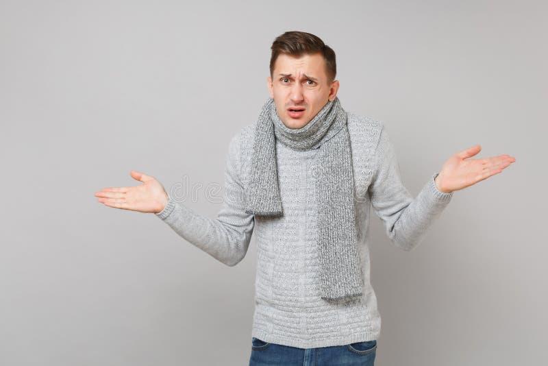 Μπερδεμένος νεαρός άνδρας στο γκρίζο πουλόβερ, χέρια διάδοσης μαντίλι στο γκρίζο υπόβαθρο τοίχων, πορτρέτο στούντιο Υγιής στοκ φωτογραφία με δικαίωμα ελεύθερης χρήσης
