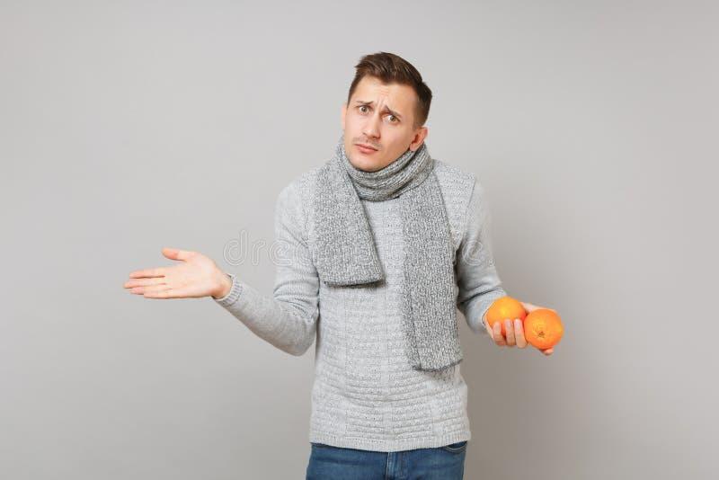 Μπερδεμένος νεαρός άνδρας στο γκρίζο πουλόβερ, χέρια διάδοσης μαντίλι, που κρατά τα πορτοκάλια στο γκρίζο υπόβαθρο τοίχων Υγιής στοκ εικόνες