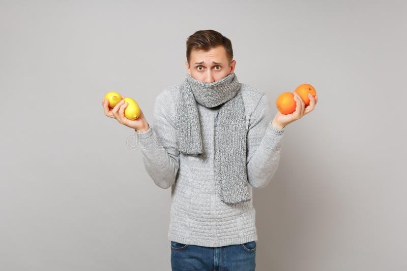 Μπερδεμένος νεαρός άνδρας στο γκρίζο πουλόβερ που καλύπτει το στόμα με τα πορτοκάλια εκμετάλλευσης μαντίλι, λεμόνια στο γκρίζο υπ στοκ εικόνα