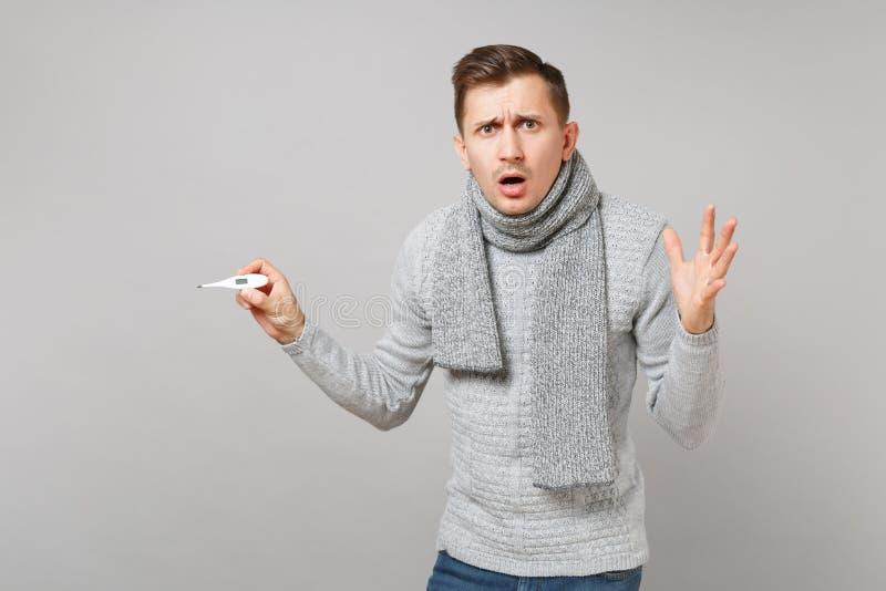 Μπερδεμένος νεαρός άνδρας στο θερμόμετρο εκμετάλλευσης μαντίλι, χέρια διάδοσης, που κρατά το στόμα ανοικτό στο γκρίζο υπόβαθρο στοκ φωτογραφία με δικαίωμα ελεύθερης χρήσης