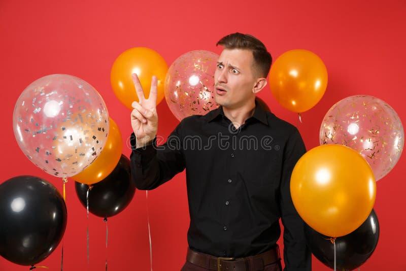 Μπερδεμένος νεαρός άνδρας στο μαύρο κλασικό εορτασμό πουκάμισων, που παρουσιάζει σημάδι νίκης στα κόκκινα μπαλόνια αέρα υποβάθρου στοκ φωτογραφίες