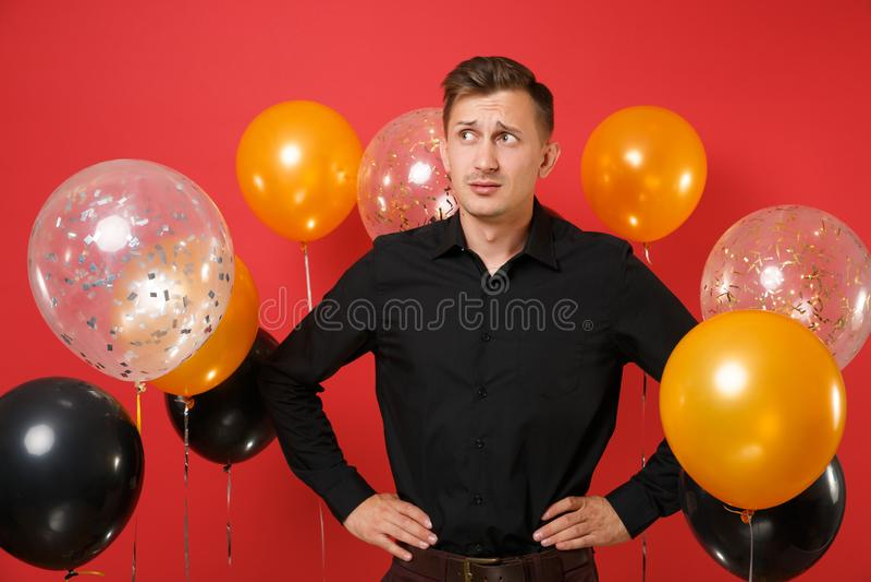 Μπερδεμένος νεαρός άνδρας στο μαύρο κλασικό πουκάμισο που στέκεται με τα όπλα σε μεσολαβή στα φωτεινά κόκκινα μπαλόνια αέρα υποβά στοκ εικόνα