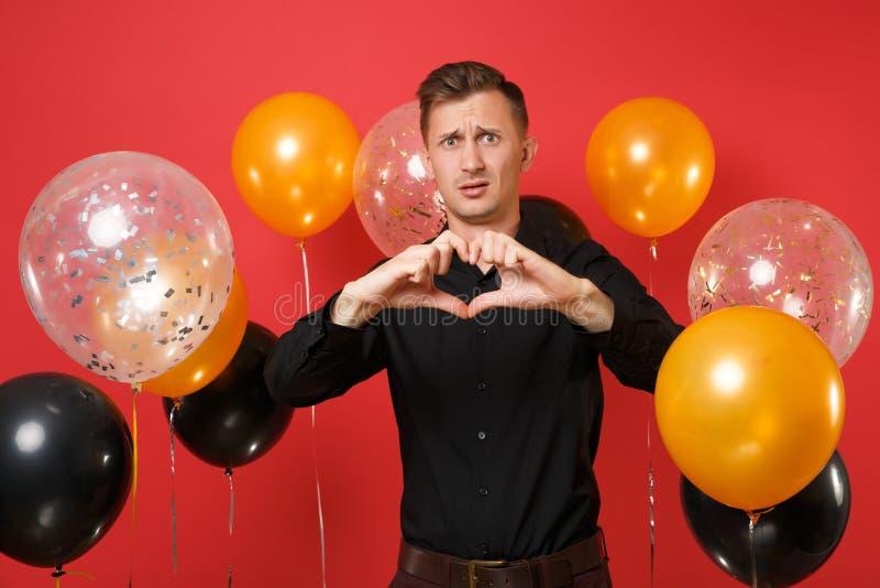 Μπερδεμένος νεαρός άνδρας στο μαύρο κλασικό πουκάμισο που παρουσιάζει χειρονομία καρδιών στα φωτεινά κόκκινα μπαλόνια αέρα υποβάθ στοκ εικόνες