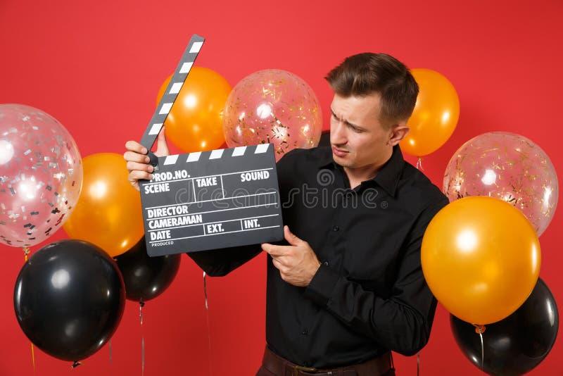 Μπερδεμένος νεαρός άνδρας στο μαύρο πουκάμισο που κοιτάζει στην κλασική μαύρη παραγωγή ταινιών clapperboard στα χέρια στο φωτεινό στοκ φωτογραφία με δικαίωμα ελεύθερης χρήσης