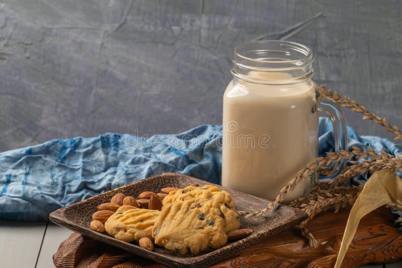 Μπισκότα αμυγδάλων στο ξύλινα πιάτο και το γάλα στοκ εικόνα