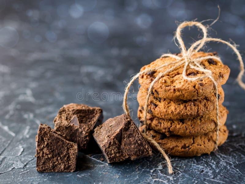 Μπισκότα σοκολάτας, που συσσωρεύονται και που δένονται με ένα σχοινί, κομμάτια της μαύρης σοκολάτας, σε ένα κατασκευασμένο υπόβαθ στοκ εικόνα με δικαίωμα ελεύθερης χρήσης