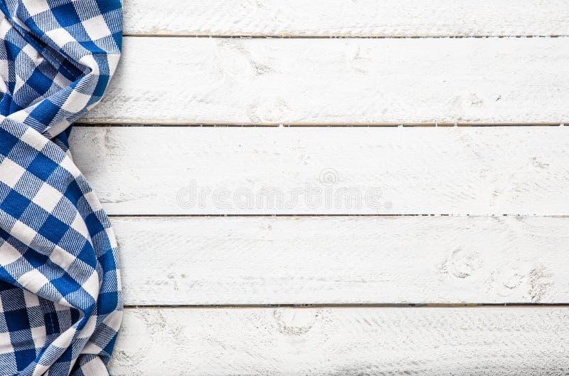 Μπλε ελεγμένο τραπεζομάντιλο κουζινών στον ξύλινο πίνακα στοκ φωτογραφίες με δικαίωμα ελεύθερης χρήσης