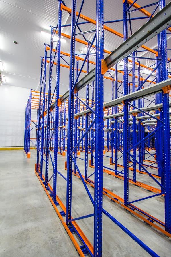 μπλε και πορτοκαλιά ράφια μετάλλων για την αποθήκευση των αγαθών σε μια μεγάλη αποθήκη εμπορευμάτων σύνθετη στοκ εικόνα