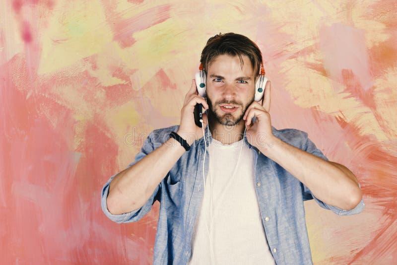 Μπλε eyed μοντέρνο hipster με το smartphone Αμερικανικός όμορφος γενειοφόρος τύπος με τα ακουστικά Ο ευρωπαϊκός τύπος έχει το χρό στοκ φωτογραφίες