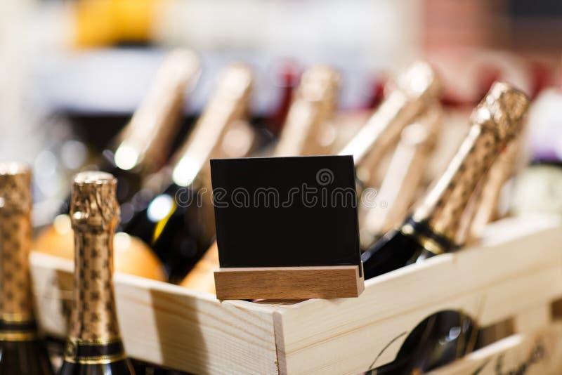 Μπουκάλια της σαμπάνιας στα ξύλινα κιβώτια με το κενό μαύρο σημάδι στοκ φωτογραφία με δικαίωμα ελεύθερης χρήσης