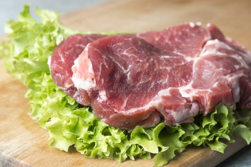 Μπριζόλες κρέατος κρέας-λαιμών στο μαρούλι στο υπόβαθρο των ραδικιών, ντομάτα, κόκκινα πιπέρια τσίλι, κίτρινα πιπέρια τσίλι, πράσ στοκ φωτογραφία με δικαίωμα ελεύθερης χρήσης