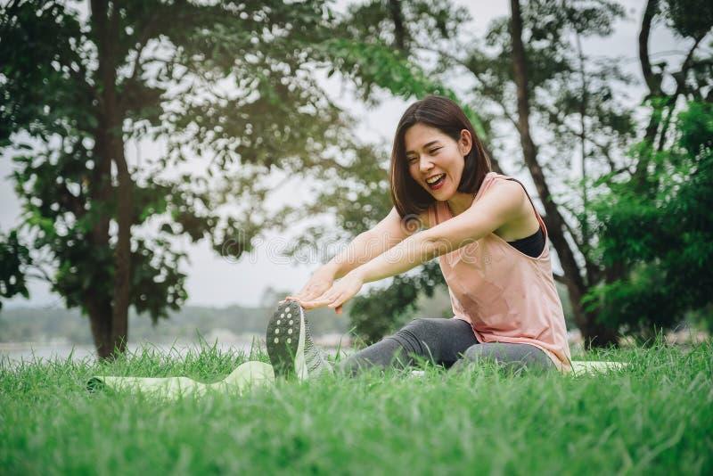 Νέα άσκηση χαμόγελου γυναικών στο πάρκο υγιής τρόπος ζωής έννοιας στοκ φωτογραφία