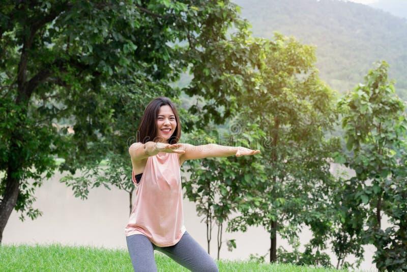 Νέα άσκηση χαμόγελου γυναικών στο πάρκο υγιής τρόπος ζωής έννοιας στοκ εικόνα