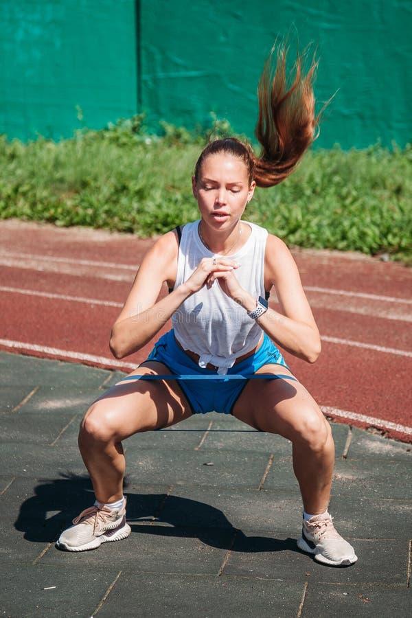 Νέα αθλήτρια που κάνει τις στάσεις οκλαδόν με την ελαστική ζώνη ικανότητας υπαίθρια στοκ φωτογραφία με δικαίωμα ελεύθερης χρήσης
