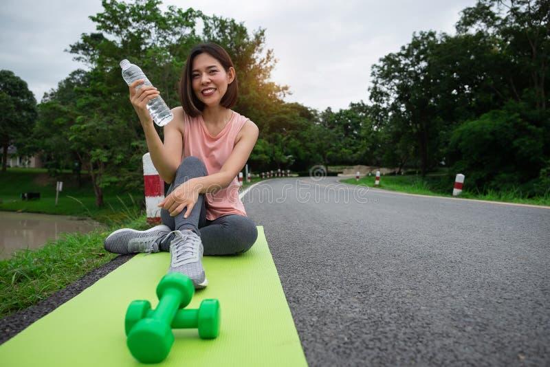 Νέα γυναίκα ικανότητας που χαμογελά και που κρατά το πόσιμο νερό μετά από τη γιόγκα στο πάρκο υγιής τρόπος ζωής έννοιας στοκ εικόνες με δικαίωμα ελεύθερης χρήσης