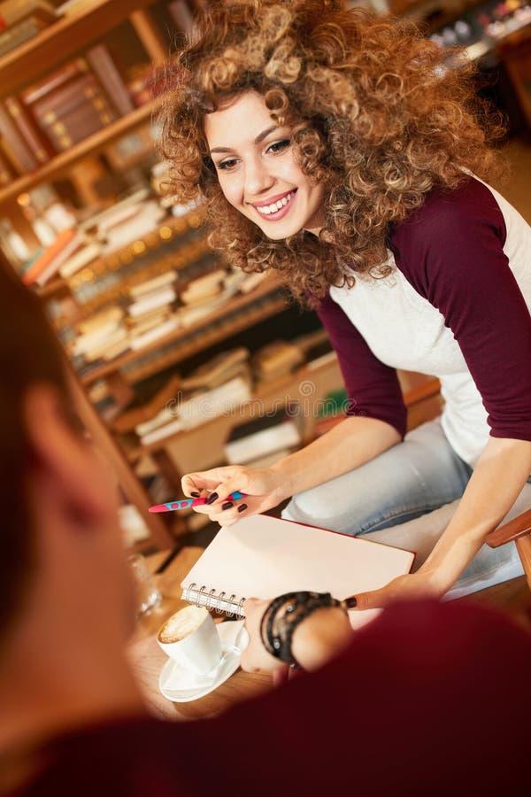 Νέα γυναίκα με τη συζήτηση φίλων στον καφέ στοκ εικόνα με δικαίωμα ελεύθερης χρήσης