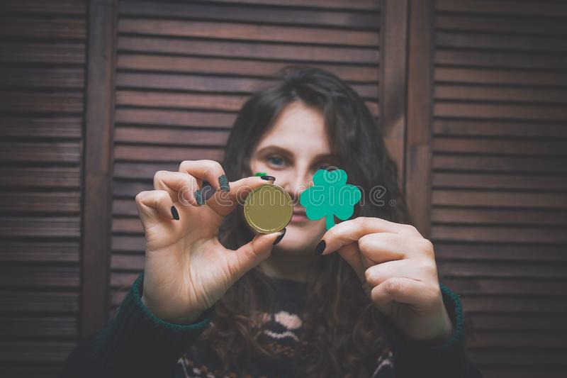 Νέα γυναίκα με το χρωματισμένο πράσινο τριφύλλι στο μάγουλό της που κρατά το χρυσό νόμισμα στο φραγμό μπροστά από έναν ξύλινο τοί στοκ εικόνα με δικαίωμα ελεύθερης χρήσης
