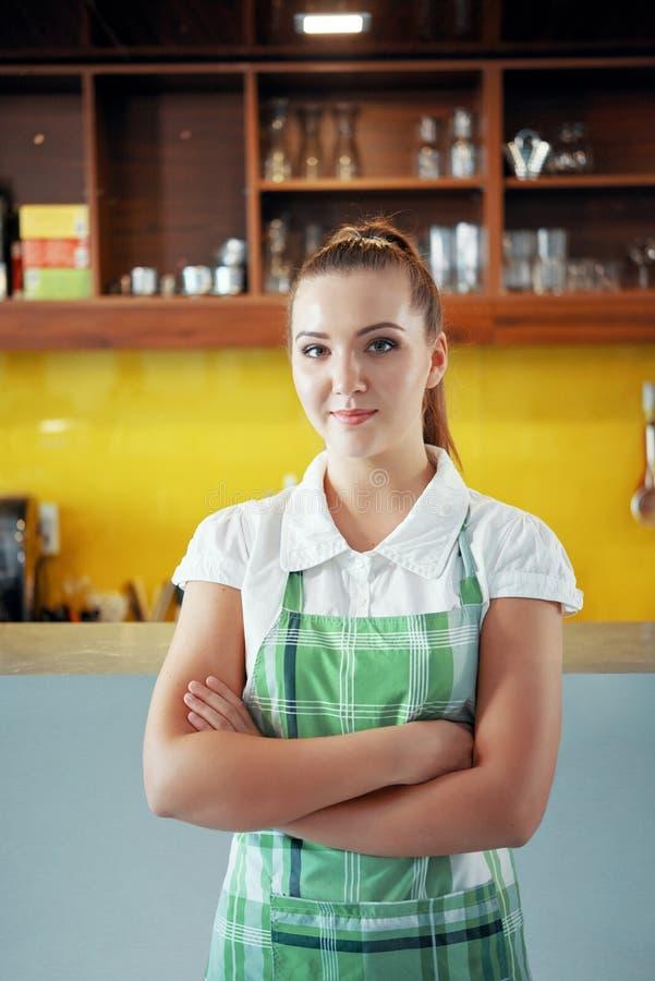 Νέα γυναίκα στην ποδιά που λειτουργεί στη καφετερία στοκ φωτογραφία με δικαίωμα ελεύθερης χρήσης