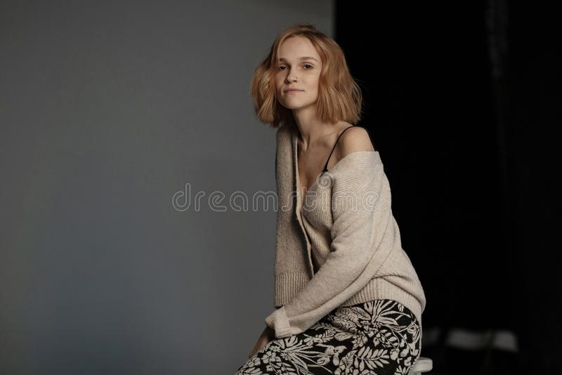 Νέα γυναίκα στο πουλόβερ με να διαπερνήσει στη συνεδρίαση μύτης της στην καρέκλα στοκ εικόνα