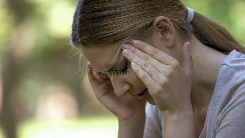 Νέα γυναίκα που υφίσταται τον οξύ πονοκέφαλο, που ανησυχεί για τις αποτυχίες, αγχωτική ημέρα στοκ φωτογραφίες