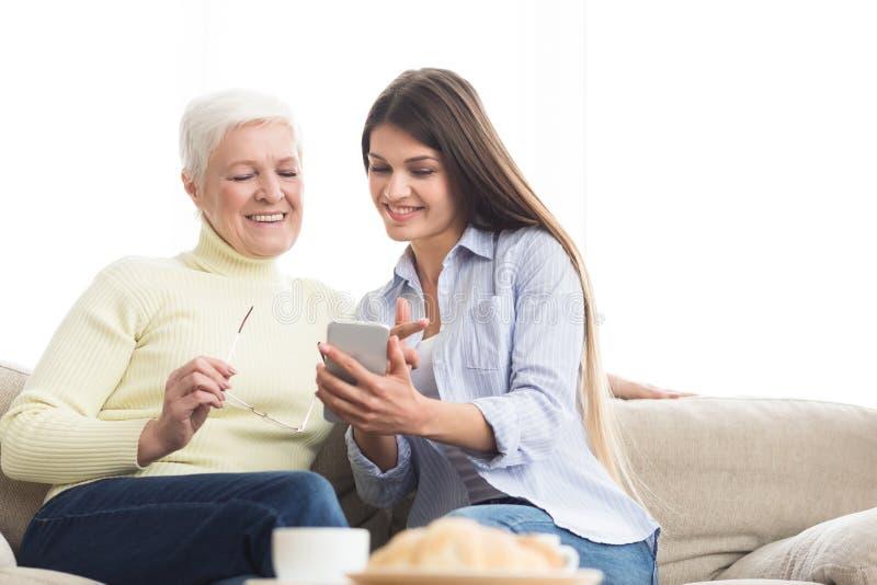 Νέα γυναίκα που παρουσιάζει φωτογραφίες στη μητέρα, που χρησιμοποιεί το smartphone στοκ φωτογραφία