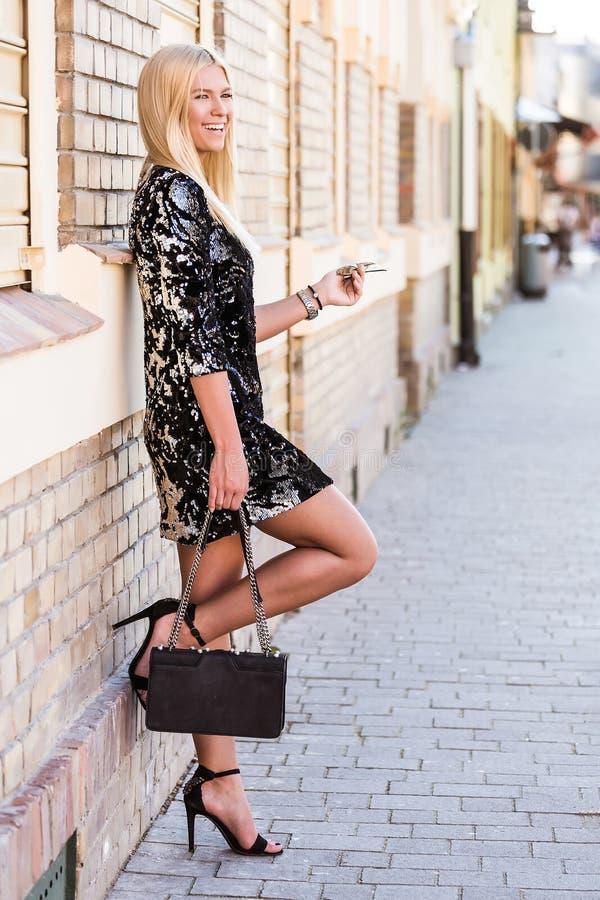 Νέα ελκυστική γυναίκα στεμένος ενάντια στον τοίχο στοκ εικόνα