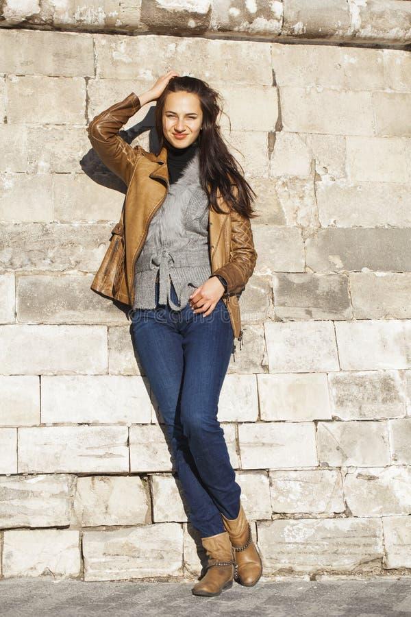 Νέα ευτυχής γυναίκα στο καφετί σακάκι δέρματος στοκ φωτογραφίες