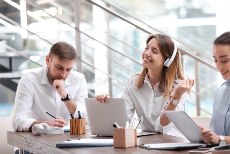 Νέα επιχειρηματίας με τα ακουστικά, το lap-top και τους συναδέλφους της στην αρχή στοκ φωτογραφίες με δικαίωμα ελεύθερης χρήσης
